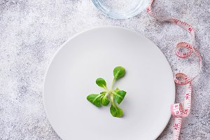 Plate with salad leaves, water and measuring tape
