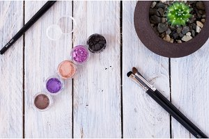 Multicolored cosmetics on the table. Cosmetics, brushes and flowerpot.