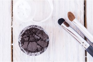 A jar of mineral cosmetics with a sifter and brushes. View from above.