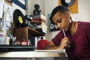 Teenage boy doing work thinking