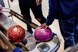Girl picking up a bowling bal