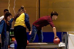 Caucasian boy picking up a bowling