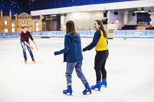 Teenage friends ice skating