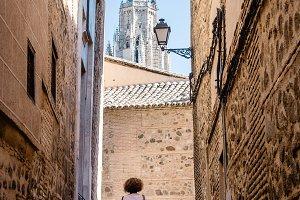Woman walking by narrow street