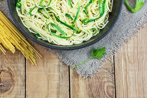 Pasta with zucchini on dark wooden b