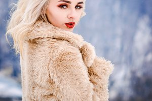 Bright girl in a beige fur coat pose