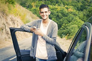 young man with car and mobile phone