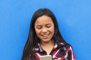 Latino girl using the mobile.