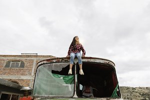 Girl sitting on the abandoned truck.