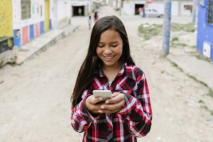 Latino girl using the mobile.