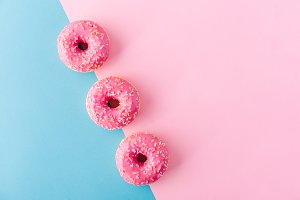 Donuts in a row on pink blue