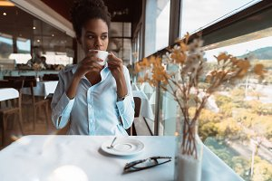 Black girl with cup of coffee indoor