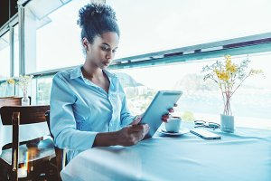 Black woman in cafe with tablet pc