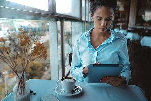 Afro woman with tablet pc in cafe