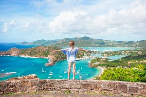 Little adorable kid with beautiful famous view. View of English Harbor from Shirley Heights, Antigua, paradise bay at tropical island in the Caribbean Sea