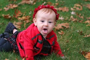 Silly baby girl playing in leaves