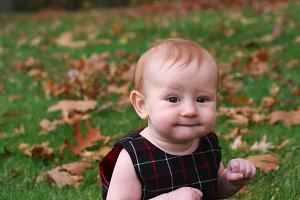 Baby girl playing in leaves vertical