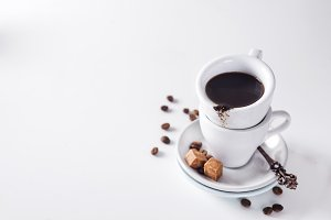 cup of black coffee on a saucer with brown sugar on a white background