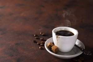 cup of black coffee on a saucer with brown sugar on a stone brown background
