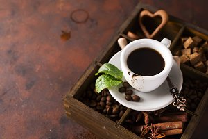 Cup of coffee with cooffee beans on a wooden box with grains of coffee and spices on a stone background