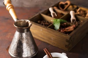 Cup of coffee with cooffee beans, wooden box with grains of coffee and spices, cezve on a stone background