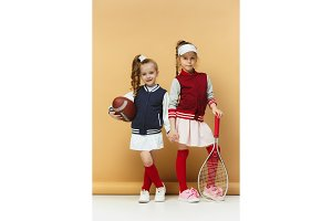 Two happy and beautyful children show different sport. Studio fashion concept. Emotions concept.
