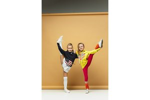 Two happy children show different sport. Studio fashion concept. Emotions concept.