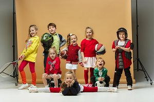 Group of happy children show different sport. Studio fashion concept. Emotions concept.