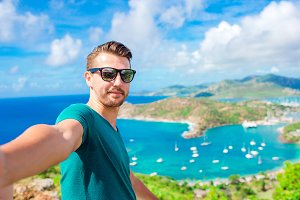 Young man taking selfie with view of English Harbor from Shirley Heights, Antigua, paradise bay at tropical island in the Caribbean Sea