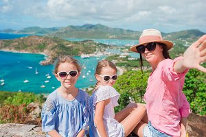Mother and kids taking selfie with view of English Harbor from Shirley Heights, Antigua, paradise bay at tropical island in the Caribbean Sea