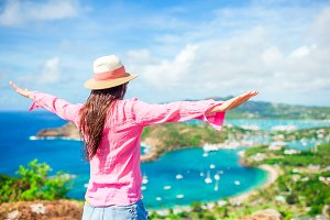 Young tourist woman with view of English Harbor from Shirley Heights, Antigua, paradise bay at tropical island in the Caribbean Sea