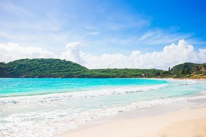 Idyllic tropical beach with white sand, turquoise ocean water and blue sky on Caribbean island