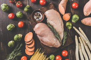 Raw chicken breasts and vegetables