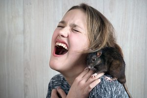 Girl in horror shouts. On a shoulder girls rat. Stunningly emotional portrait