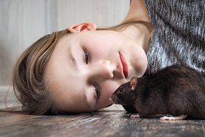 The girl lying on the floor looks at the rat