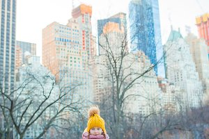 Adorable little girl with view of ice-rink in Central Park on Manhattan in New York City