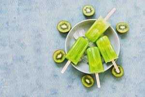 Frozen kiwi smoothie on a stick .