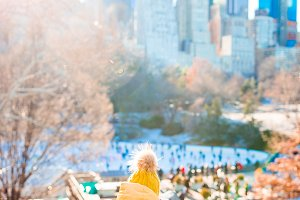 Adorable little girl with view of ice-rink in Central Park at New York City