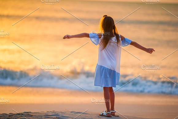 Adorable Happy Little Girl Walking On White Beach At Sunset