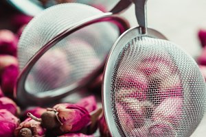 Rose buds and tea strainer close up.