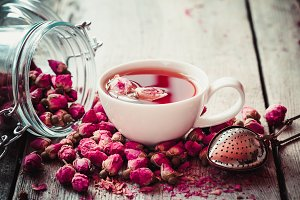 Rose tea, strainer, jar of rosebuds.