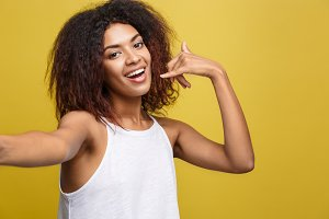 Close-up Cheerful young beatiful African American woman taking a selfie herself and make phone symbol by hand. Yellow studio background. Copy Space.