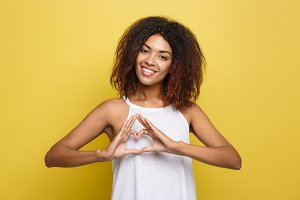 Isolated portrait of beautiful African American make heart symbol by hands. Yellow studio background. Copy Space.