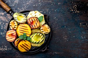 GRILLED FRUITS. Grill fruits - pineapple, peaches, plums, avocado, pear on black cast iron grill pan. Dark background. Top view. Copy space