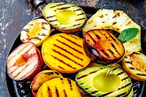 GRILLED FRUITS. Grill fruits - pineapple, peaches, plums, avocado, pear on black cast iron grill pan. Dark background. Top view