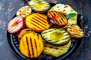 GRILLED FRUITS. Grill fruits - pineapple, peaches, plums, avocado, pear on black cast iron grill pan. Dark background.