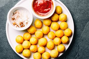 Fried potatoes ball, crocettes on white plate with tomato sauce,