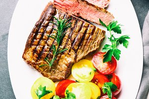 Sliced medium rare grilled beef steak served on white plate with
