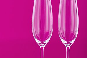 Two wine glasses with rose and candle on pink