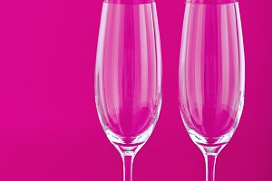 Two wine glasses with rose flower on pink